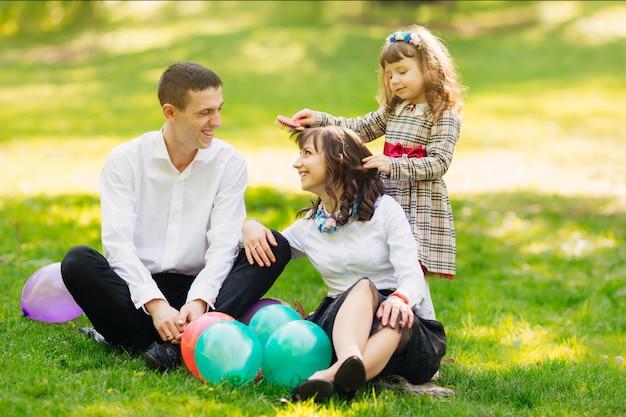 La famille est assise sur une pelouse avec des ballons