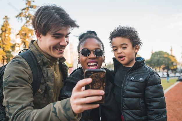 Famille ethnique de race mixte prenant selfie.