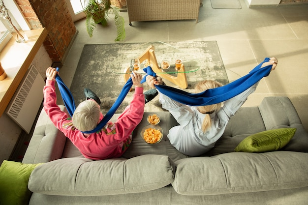 Famille excitée en regardant le football, match de sport à la maison. grand-mère et fille acclamant émotionnellement l'équipe nationale de basket-ball, football, tennis, soccer, hockey. concept d'émotions, de soutien, d'encouragement.