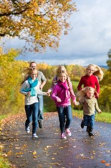 Famille faire une promenade dans la forêt d'automne