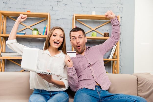 Famille faisant des achats sur internet avec ordinateur portable et carte bancaire