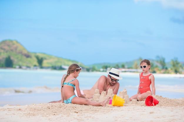 Famille faisant le château de sable à la plage blanche tropicale