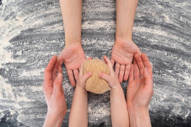 La famille fait des biscuits dans la cuisine. les mains de la mère et de ses deux enfants sont avec de la pâte. vue de dessus