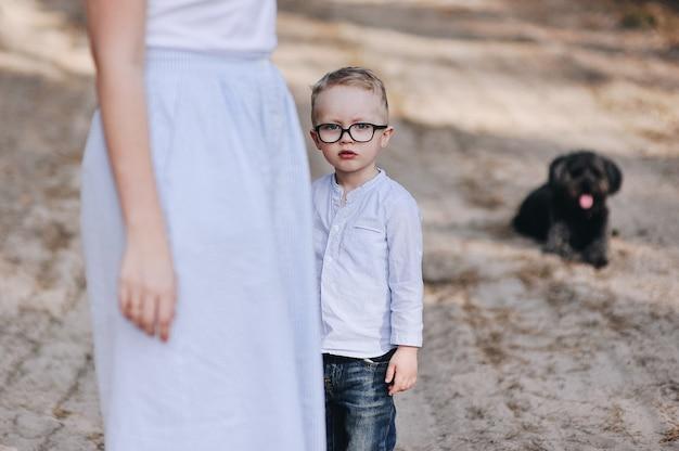 La famille fait un pique-nique dans la forêt. fils a maman. promenade d'été. ensemble de pique-nique. chien. l'enfant à lunettes.