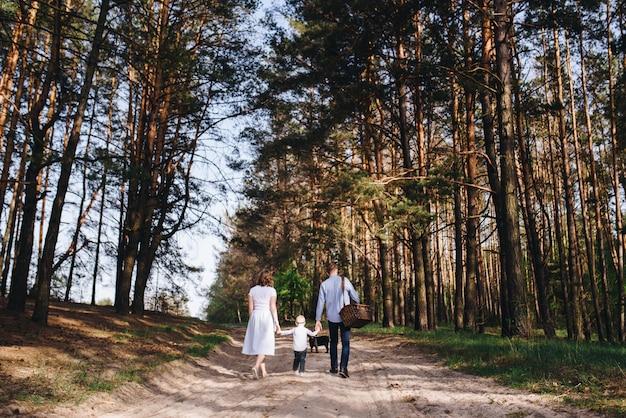 La famille fait un pique-nique dans la forêt. maman, papa, fils. promenade d'été. ensemble de pique-nique. chien. l'enfant à lunettes. vêtements bleus. belle famille.