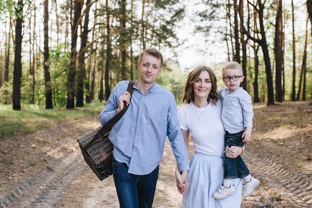 La famille fait un pique-nique dans la forêt. maman, papa, fils. su