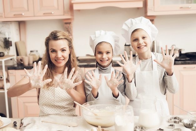 Famille familiale de cuisson fait la pâte les mains dans la farine.