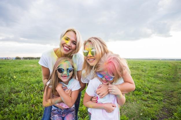 Famille, festival de holi et concept de vacances - gros plan portrait de mères et filles couvertes de peinture.