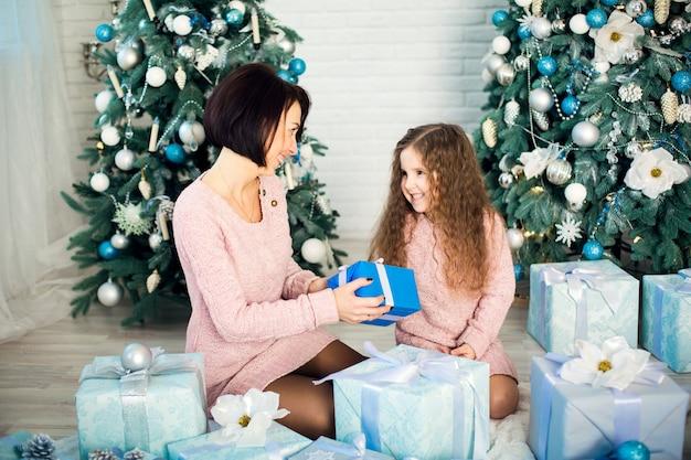La famille fête noël sapin de noël . maman et sa fille se donnent des cadeaux de noël. coffrets cadeaux. joyeux noël et joyeuses fêtes. enfance heureuse.