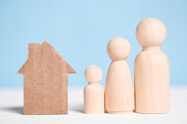 Famille de figures en bois avec maison en carton sur bleu.