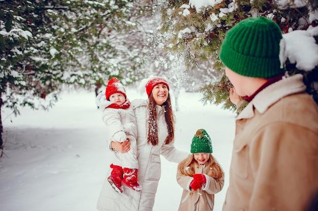 Famille avec filles mignonnes dans un parc d'hiver