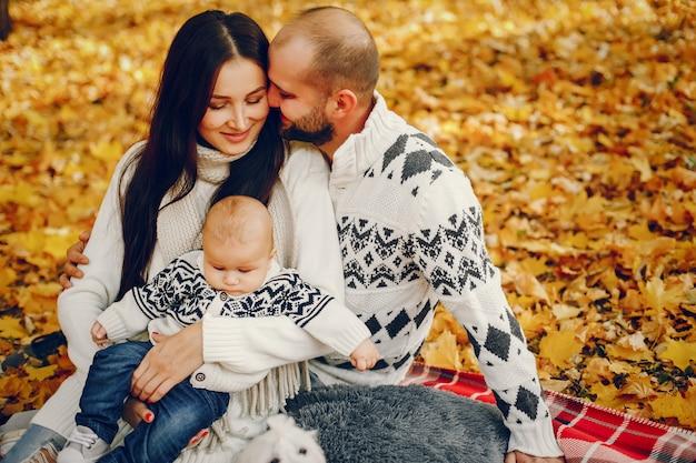 Famille avec fils dans un parc en automne
