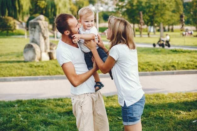Famille avec fils jouant dans un parc d'été