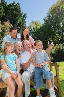 Famille de génération multi assis sur un banc en prenant la photo d'eux-mêmes