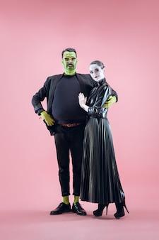 Famille D'halloween. Couple Heureux En Costume D'halloween Et Maquillage. Thème Sanglant : Le Maniaque Fou Fait Face Sur Fond De Studio Rose Photo Premium