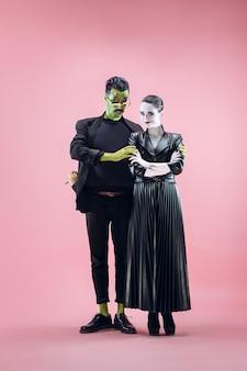 Famille d'halloween. couple heureux en costume d'halloween et maquillage. thème sanglant : le maniaque fou fait face sur fond de studio rose
