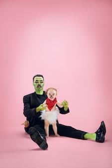 Famille d'halloween. heureux père et enfants fille nouveau-née en costume d'halloween et maquillage. thème sanglant : le maniaque fou sur fond de studio rose