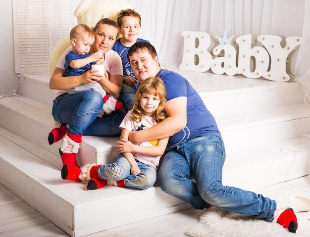 Famille heureuse avec 3 enfants assis sur le sol du salon à la maison.