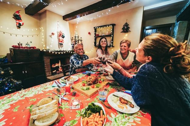Famille heureuse acclamant avec du vin rouge tout en mangeant le dîner de noël ensemble - concentrez-vous sur les mains tenant des lunettes