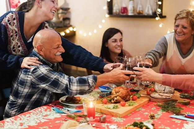 Famille heureuse acclamant avec du vin tout en mangeant le dîner de noël ensemble - concentrez-vous sur les mains tenant des verres