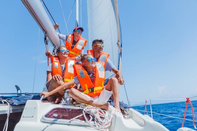 Famille heureuse avec adorable fille et fils reposant sur un grand yacht