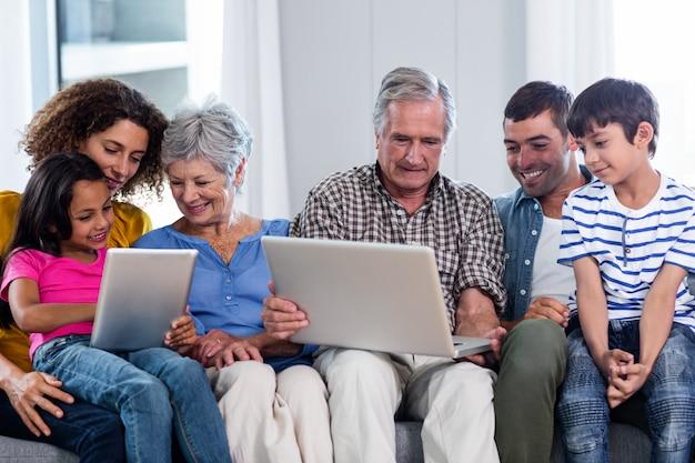 Famille heureuse à l'aide d'un ordinateur portable et d'une tablette numérique dans le salon