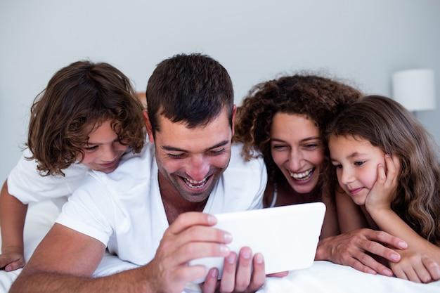 Famille heureuse à l'aide d'une tablette numérique sur le lit