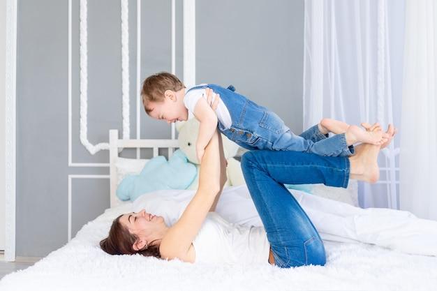 Une famille heureuse et aimante. maman et bébé jouent à la maison sur le lit, s'amusent et rient.