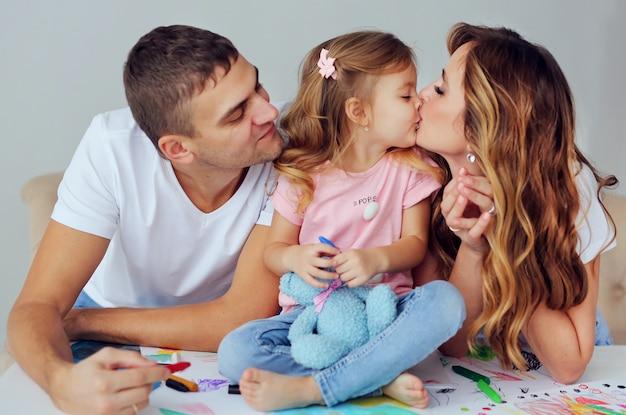 Famille heureuse d'apparence européenne. des parents souriants jouent et apprennent à dessiner leur jolie petite fille. un homme et une belle femme avec un enfant s'amusent.