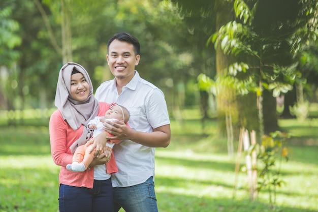 Famille heureuse asiatique avec bébé nouveau-né dans le parc