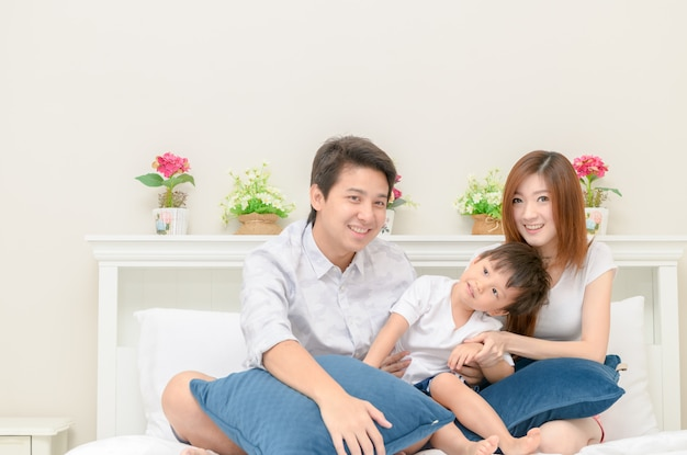 Famille heureuse asiatique sur un lit blanc dans la chambre