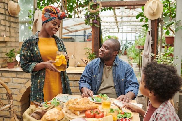 Famille heureuse assise à table avec de la nourriture et se parlant pendant le déjeuner dans le jardin