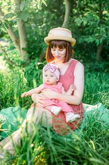 Une famille heureuse ayant un pique-nique dans le jardin vert dans une journée de printemps ensoleillée: une belle mère souriante assise sur l'herbe verte et sa petite fille qui rit sur ses jambes