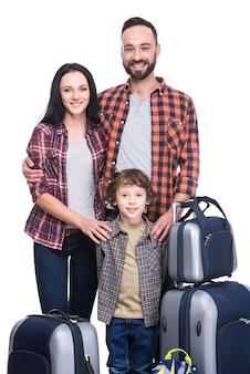 Une famille heureuse avec des bagages est prête à voyager.