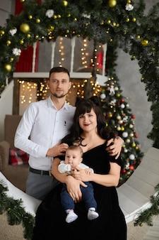 Famille heureuse avec un bébé célébrant noël