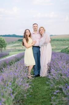 Famille heureuse, bel homme mûr, femme magnifique et fille de jeune fille assez agréable, posant ensemble dans un champ de lavande