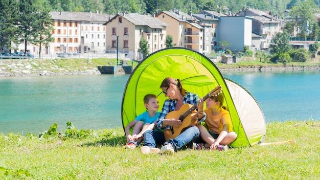 Une famille heureuse campant au bord de la rivière, jouant de la guitare et chantant une chanson ensemble dans la tente.