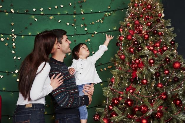 Famille heureuse célébrant le nouvel an et debout près de l'arbre de noël.
