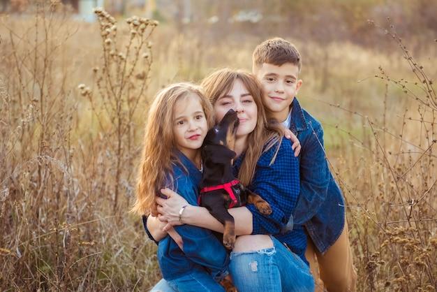 Famille heureuse avec un chien teckel dans le parc d'automne