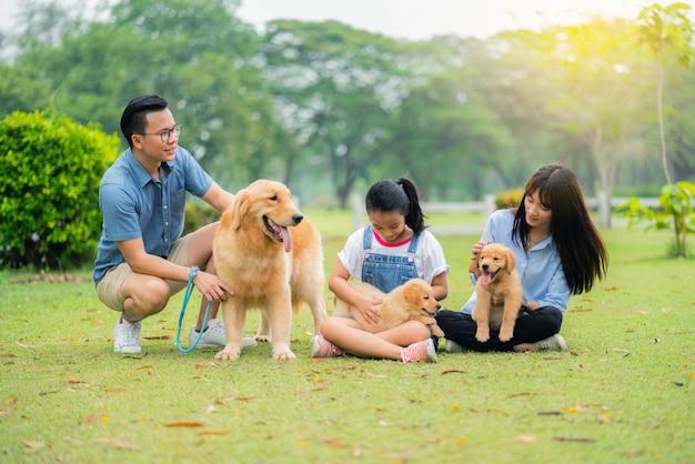 Famille heureuse et les chiens heureux dans le jardin