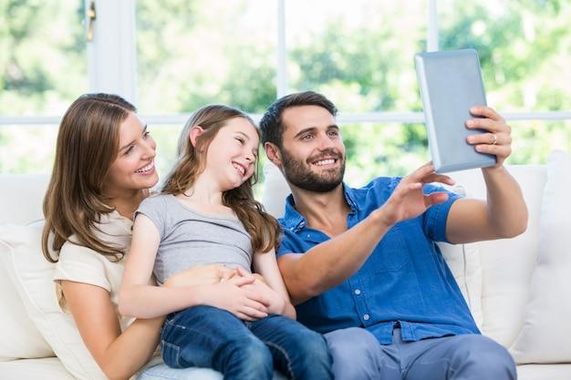 Famille heureuse en cliquant sur selfie avec tablette numérique