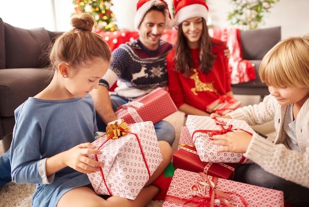 Une famille heureuse commence à ouvrir les cadeaux de noël