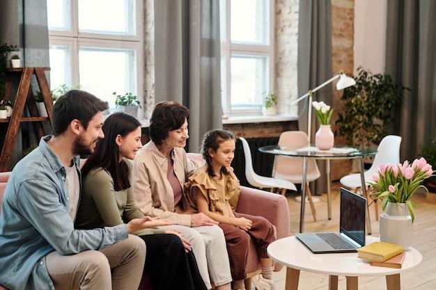 Famille heureuse communiquant par chat vidéo dans un environnement domestique