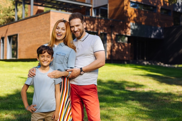 Famille heureuse. content des parents aimants souriants et debout avec leur fils