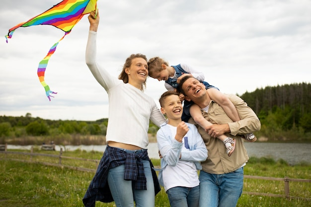 Famille heureuse de coup moyen avec un cerf-volant coloré