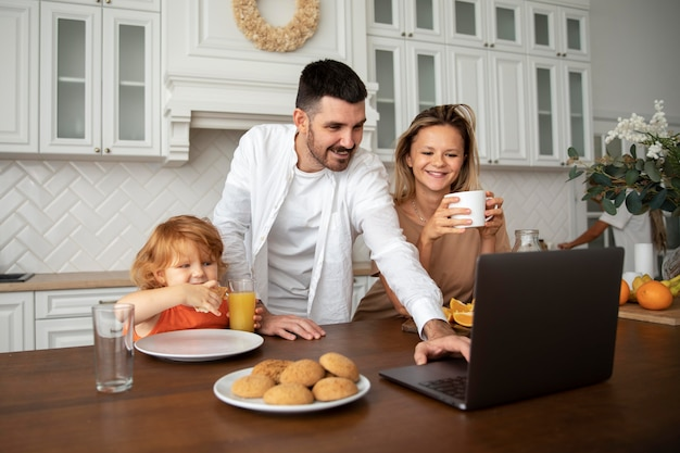 Famille heureuse de coup moyen avec ordinateur portable