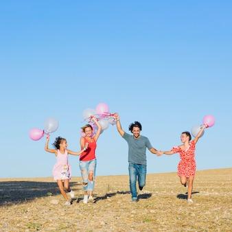 Famille heureuse, courir avec des ballons