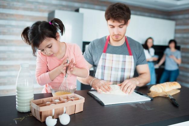 Une famille heureuse cuisine dans la cuisine. le père apprend à sa fille à couper les légumes. mère et grand-mère se tiennent dans le mur. ils pétrissent la pâte ensemble.