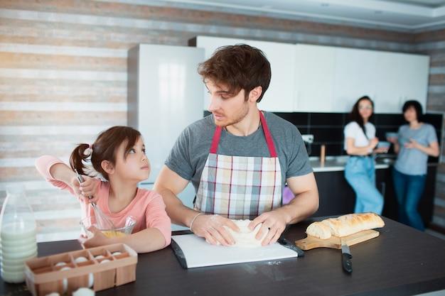 Une famille heureuse cuisine dans la cuisine. le père apprend à sa fille à couper les légumes. .