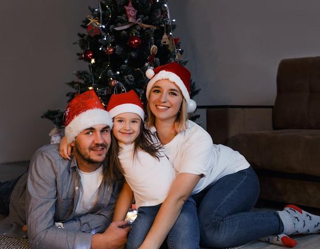 Une famille heureuse dans des chapeaux de noël se trouve près de l'arbre de noël et le sourire. tradition familiale.